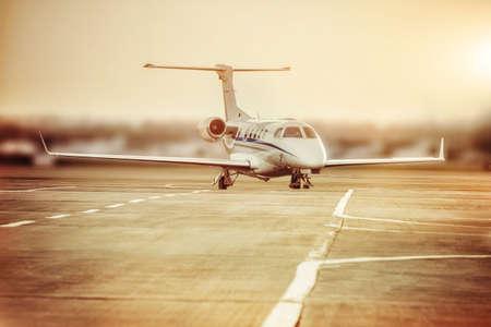 Prive-vliegtuigparkeerplaats op het vliegveld. Privé vliegtuig bij oranje zonsondergang. Stockfoto