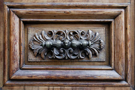 Un bouton de porte antique en forme de tête de chien sur une porte en bois. Banque d'images