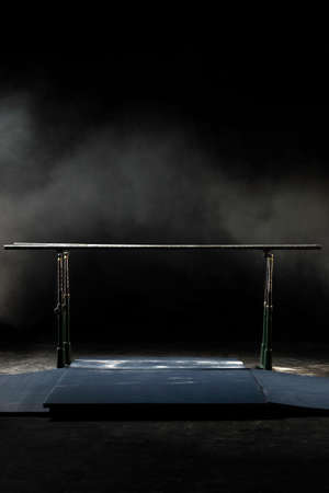 Closeup. Gymnastic parallel bars. Isolated on black background with fog, Vertical shot. Banque d'images