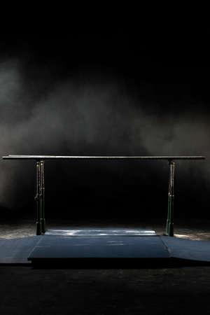 Fermer. Barres parallèles de gymnastique. Isolé sur fond noir avec brouillard, tir vertical.