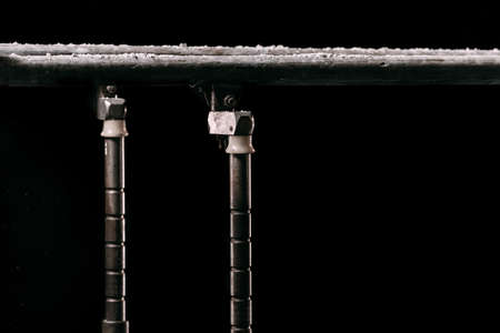 Closeup. Talcium powder over gymnastic parallel bars. Gymnastic parallel bars. Isolated on black background with fog,