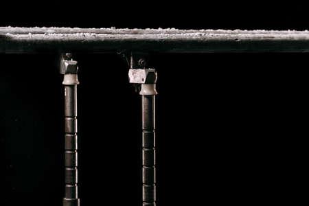 Fermer. Poudre de talcium sur des barres parallèles de gymnastique. Barres parallèles de gymnastique. Isolé sur fond noir avec du brouillard,