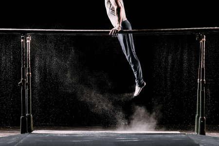 Athlète masculin effectuant un handstand sur des barres parallèles de gymnastique avec de la poudre de talc. Isolé sur le noir.