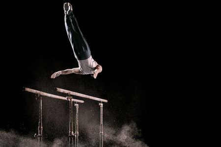 Athlète masculin exerçant un exercice difficile sur des barres parallèles de gymnastique avec de la poudre de talc. Isolé sur le noir. Banque d'images