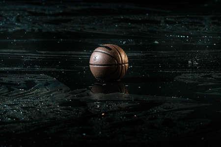 Basket-ball sur le plancher de la cour humide près d'un fond flou. Sous la pluie. Banque d'images - 78976651