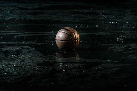 Basketball on wet Court Floor close up with blurred background. Under the rain.