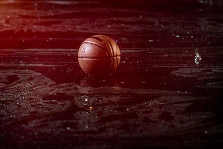 Basket-ball sur le plancher de la cour humide près d'un fond flou. Sous la pluie.