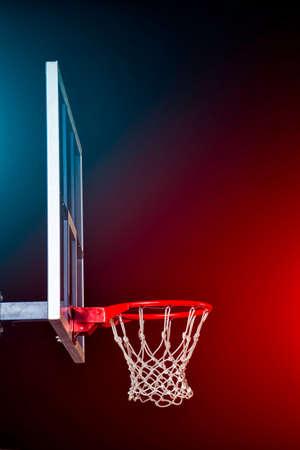Basketball isolé sur noir. Éclairé par des lumières colorées.