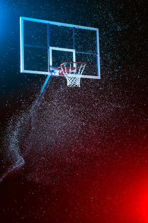 Basketball hoop isolated on black. Basketball arena under rain. Lightened by mixed color lights.