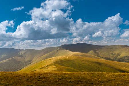 Vue d'été des Carpates et des Vallées, sous le ciel bleu avec des nuages. La route de montagne monte sur les collines sur le paysage du coucher du soleil. Banque d'images - 81867348
