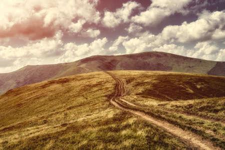 Paysage d'automne. Vue d'automne des Carpates, sous un couvert nuageux. La route de montagne monte sur les collines sur le paysage du coucher du soleil. Banque d'images - 81867346