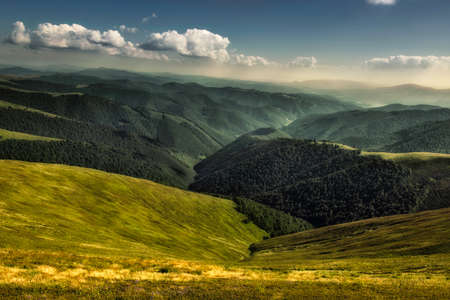 Autumn landscape. Autumn view of green Carpathian Mountains , top of the green hills on sunset landscape under blue cloudy sky.