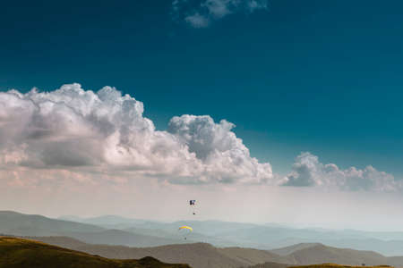Summer view of Carpathian Mountains and Valleys, under blue sky with clouds. With pair of paragliders in sky. Banque d'images