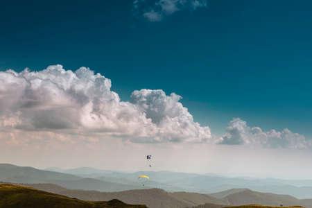 Vue d'été des Carpates et des Vallées, sous le ciel bleu avec des nuages. Avec une paire de parapentistes dans le ciel.