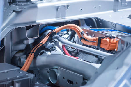 Chassis of the electric car with powertrain and power connections closeup. Blue toned.