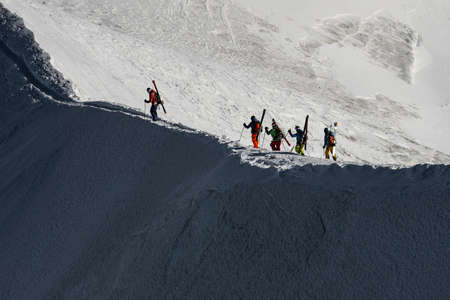 Free ride skiers, skiing down steep slope, good background with white valley and mountains in french alps. Winter sport concept with adventure guys on mountain top hiking to start point.