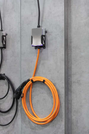 Electric car concept - electric car charging plug. Mounted on concrete wall. 스톡 콘텐츠