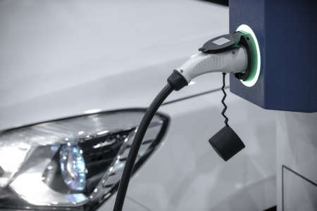 EV Car or Electric car at charging station with the power cable supply plugged in. Eco-friendly alternative energy concept