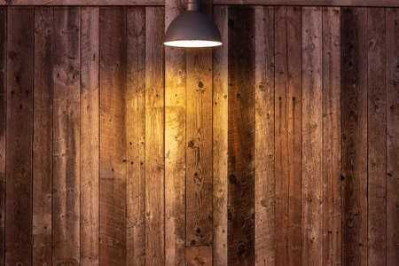 Glowing light bulb on wooden background. Light falling from old vintage lamp on wall. 스톡 콘텐츠 - 131750352