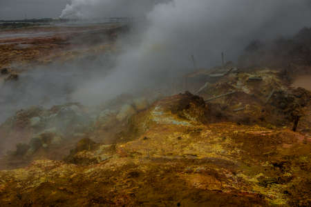 The colorful landscape at the geothermal area. Hot sulfuric steam vent spewing sulphur steam in the hot geothermal area Iceland. Color and mineral rich textured muddy ground in front