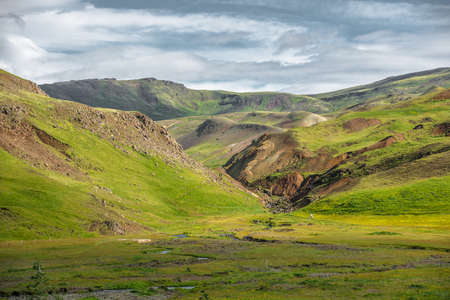 Wonderful icelandic nature landscape. View from the top. High mountains, mountain river and green grassland. Green meadows. Iceland.