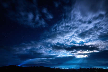 Beautiful night landscape with clouds and stars in the sky against the background of mountains with forests. Moon illuminated lanscape.