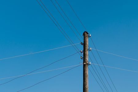 Electric wires are stretched every which way from a column