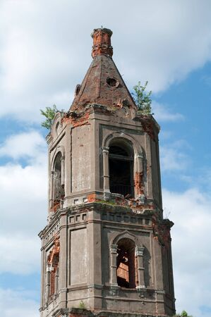 Ruins of old brick church against the blue sky with clouds