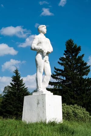 White monument to the pilot in a summer garden, against the sky with clouds