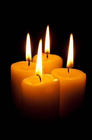 Group of four burning candles in the dark Stock Photo