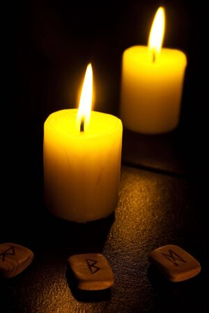 Candle and reflexion in a mirror. Nearby three fleece Stock Photo