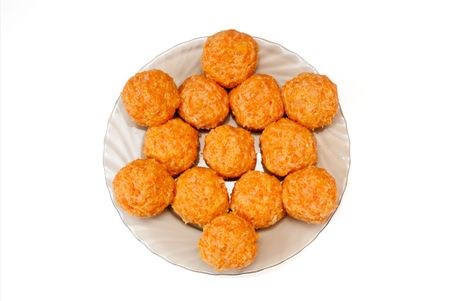 Round meatballs are spread out on a glass dish, on a white background