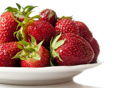 Ripe strawberry on a dish, with a shade, on a white background