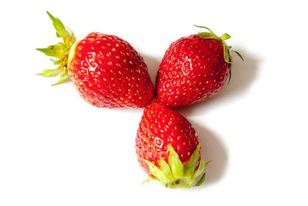 Three berries of a strawberry with a shade on a white background