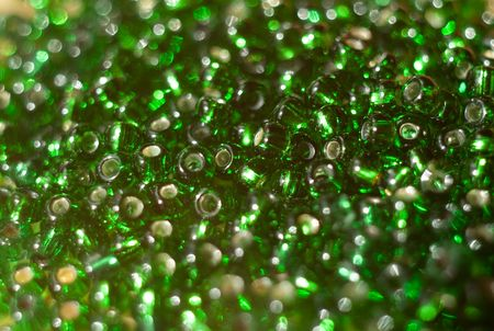 Background from the green beads scattered on an equal surface