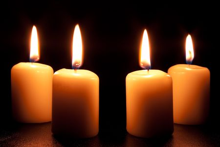 Group of four burning candles in darkness Stock Photo