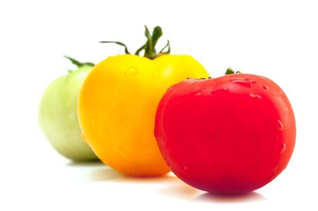 Red, yellow and green tomatoes with a shadow on a white background Stock Photo