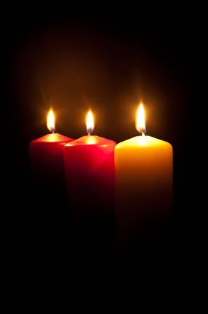 Group of three different burning candles in darkness Stock Photo - 7938319