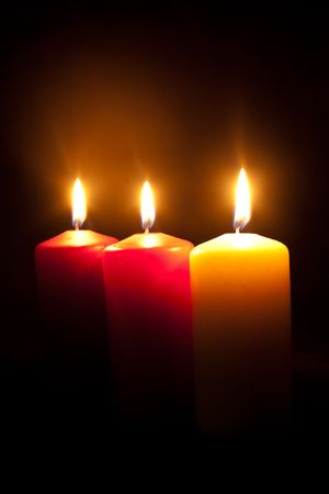 Group of three different burning candles in darkness Stock Photo - 8203182