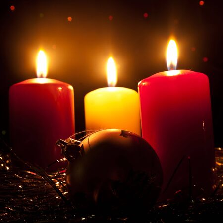 The New Year's sphere lays near to three burning candles Stock Photo - 8203183