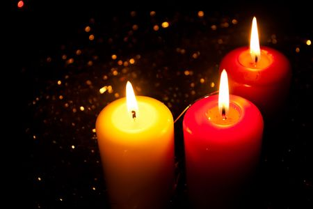 Three burning candles stand in a tinsel Stock Photo - 8203184