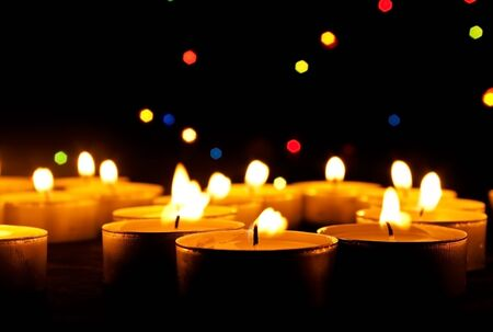 Tea candles burn on an abstract dark background Stock Photo - 10588212