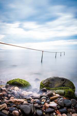 Long exposure of single post standing in flat water and pebble. pebble stones by the sea. Silky waves of blue sea from long exposure.