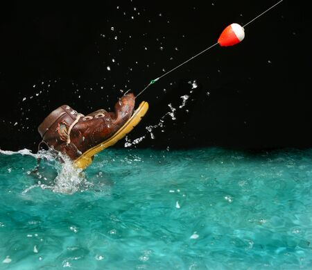 Catching an old shoe with a fishing pole. Splash of water Stock Photo - 634582