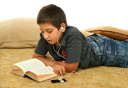 Boy studing laying down and listening with a mp4 player photo