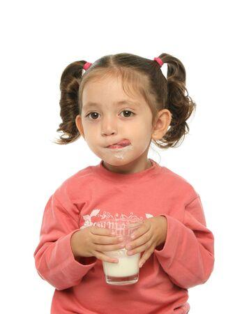 Toddler enjoying a glass of fresh milk photo