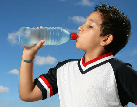 Thirsty boy drinking fresh water outdoors wearing sport clothes photo