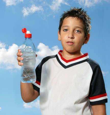 sport clothes: Thirsty boy drinking fresh water outdoors wearing sport clothes Stock Photo