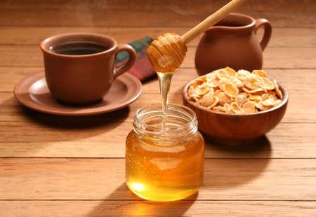 Breakfast scene. Honey pouring from glass jar photo