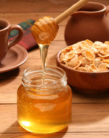 Breakfast scene. Honey pouring from glass jar Stock Photo